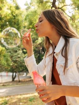 Jovem mulher fazendo bolhas de sabão em vista lateral