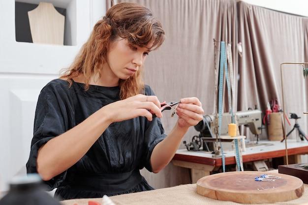 Jovem mulher fazendo brincos