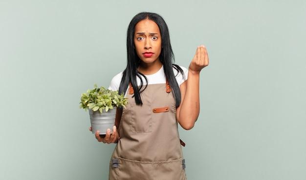 Jovem mulher fazendo capice ou gesto de dinheiro, mandando você pagar suas dívidas!