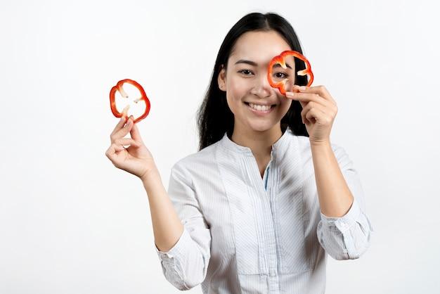 Jovem mulher fazendo cara engraçada com fatias de pimentão vermelho em fundo branco