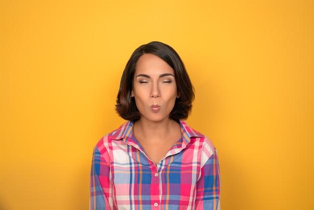 Jovem mulher fazendo caretas, olhando para a câmera. modelo feminino em camisa xadrez isolada em fundo amarelo. emoções humanas, conceito de expressão facial.