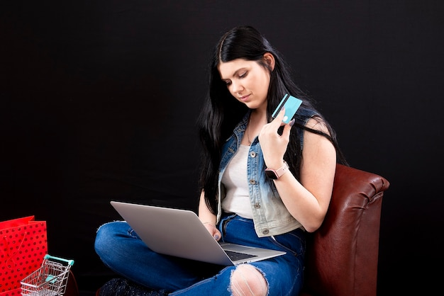 Jovem mulher fazendo compras online em casa, sentada ao lado da fileira de sacolas de compras, isolada no escuro
