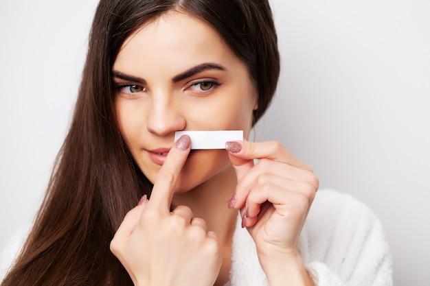 Jovem mulher fazendo depilação na área acima das sobrancelhas