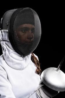 Jovem mulher fazendo esgrima em equipamento especial