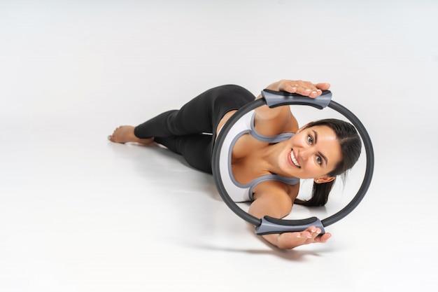 Jovem mulher fazendo exercício com círculo de pilates