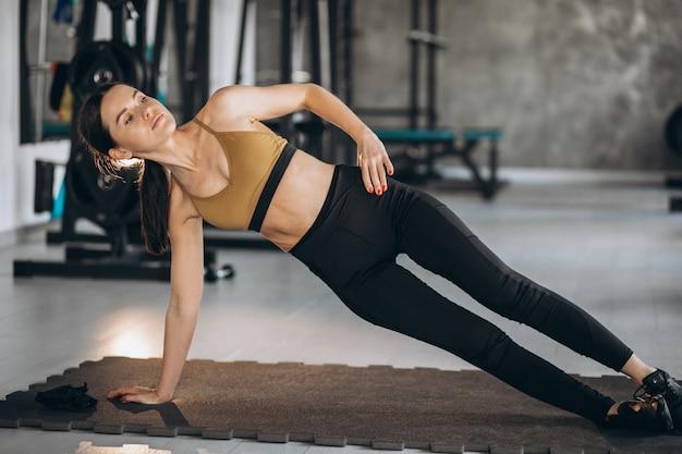 Jovem mulher fazendo exercícios abdominais na academia