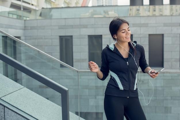 Jovem mulher fazendo exercícios ativos na rua ouvindo música