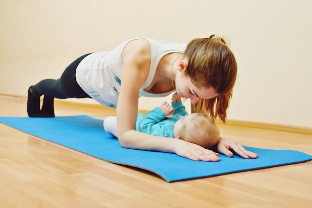 Jovem mulher fazendo exercícios com bebê