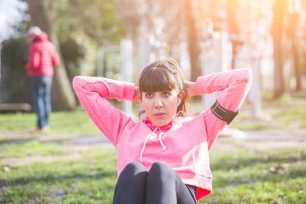 Jovem mulher fazendo exercícios de abs no parque.