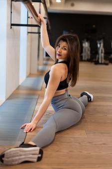 Jovem mulher fazendo exercícios de alongamento no ginásio