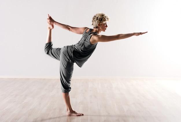 Jovem mulher fazendo exercícios de equilíbrio da ioga
