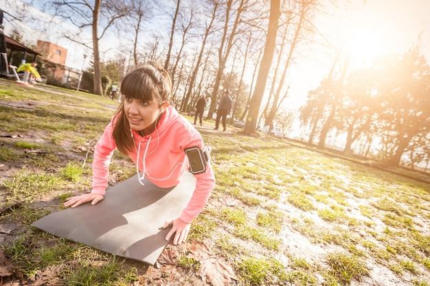 Jovem mulher fazendo exercícios de flexões no parque.