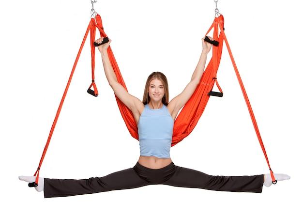 Jovem mulher fazendo exercícios de ioga antigravidade no alongamento de fio