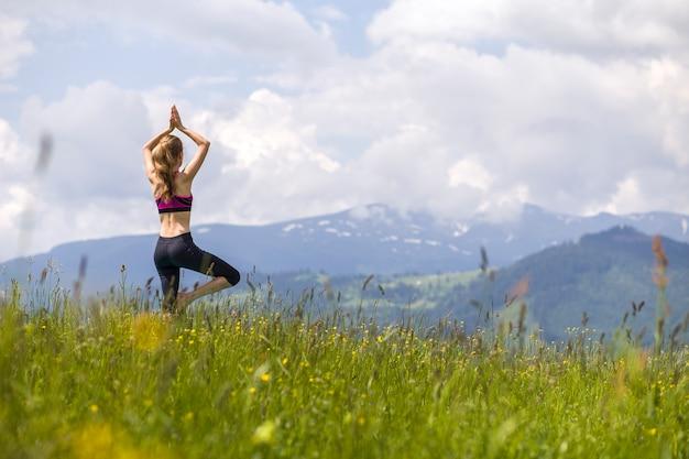 Jovem mulher fazendo exercícios de ioga ao ar livre