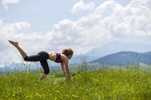 Jovem mulher fazendo exercícios de ioga ao ar livre.