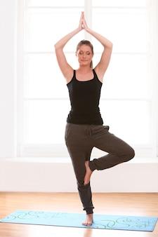 Jovem mulher fazendo exercícios de ioga em casa