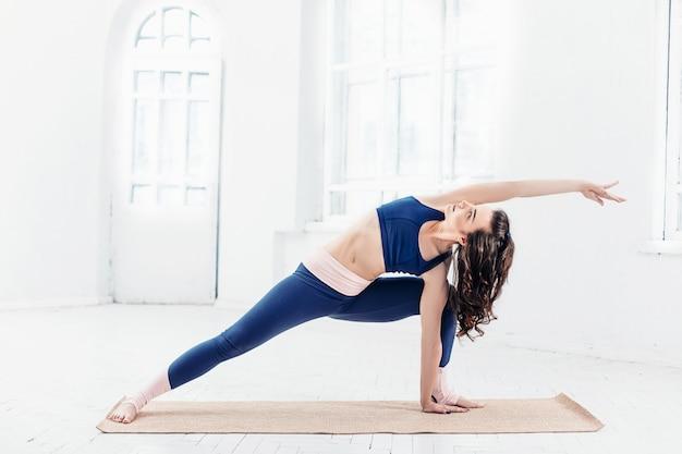 Jovem mulher fazendo exercícios de ioga