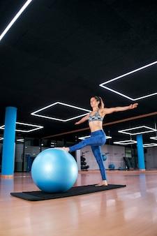 Jovem mulher fazendo exercícios de pilates na bola de fitness.