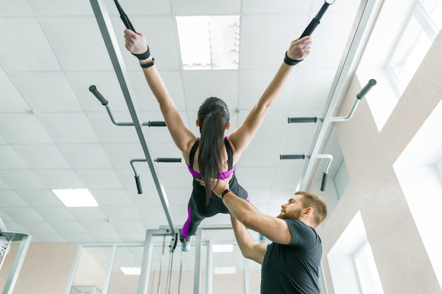 Jovem mulher fazendo exercícios de reabilitação com instrutor pessoal