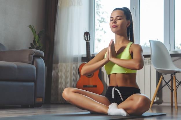 Jovem mulher fazendo exercícios de respiração no tapete de ioga em casa
