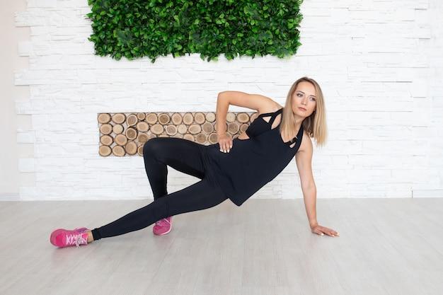 Jovem mulher fazendo exercícios indoor no chão