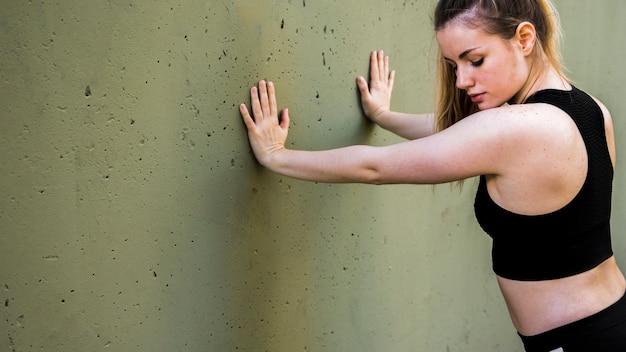 Jovem mulher fazendo exercícios na rua
