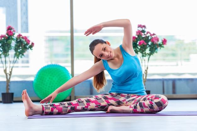 Jovem mulher fazendo exercícios no conceito de saúde de ginásio