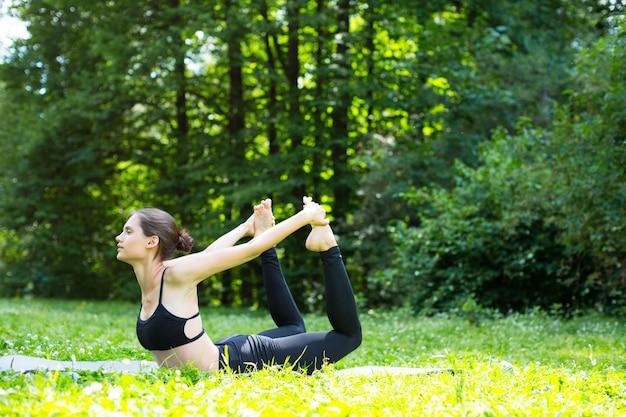Jovem mulher fazendo exercícios no parque.