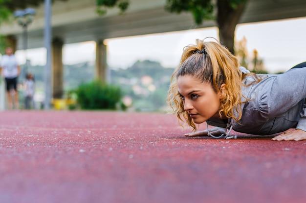 Jovem mulher fazendo flexões na pista de corrida