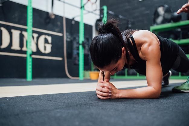 Jovem mulher fazendo flexões treinamento ginásio indoor