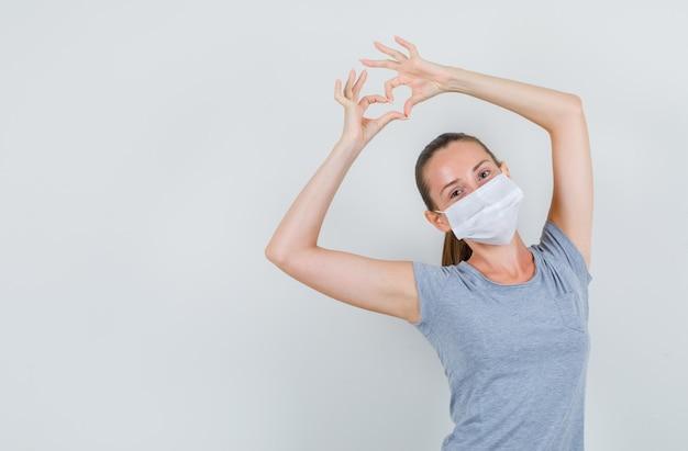 Jovem mulher fazendo formato de coração com os dedos em t-shirt, máscara e olhando alegre, vista frontal.