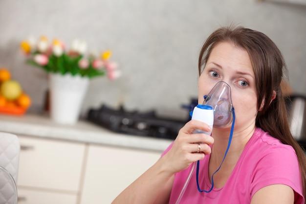 Jovem mulher fazendo inalação com um nebulizador em casa