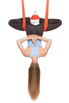 Jovem mulher fazendo ioga aérea antigravitante em rede na parede branca