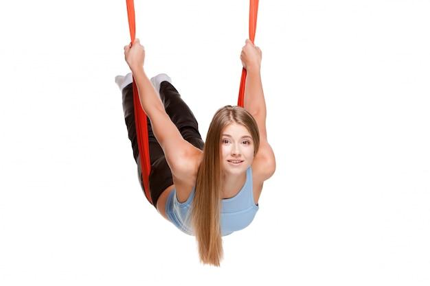 Jovem mulher fazendo ioga aérea antigravitante