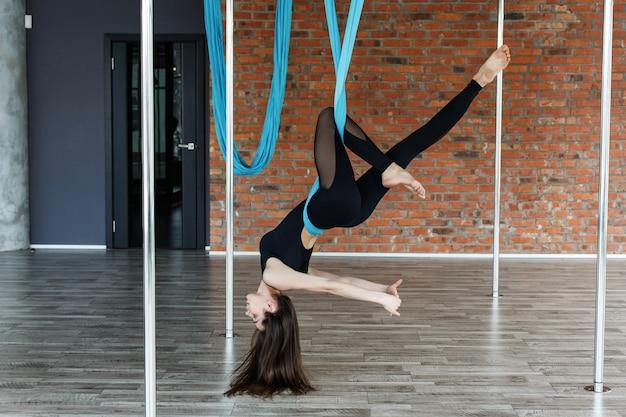 Jovem mulher fazendo ioga aérea na rede de suspensão azul no ginásio