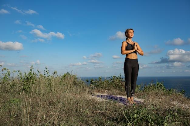 Jovem mulher fazendo ioga ao ar livre com incrível vista traseira. bali. indonésia.