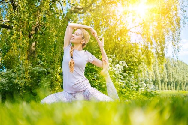 Jovem mulher fazendo ioga asana no parque, garota, exercícios de alongamento em posição de ioga, mulher feliz e saudável sentada em posição de lótus praticando ioga e meditação e esportes no pôr do sol ao ar livre