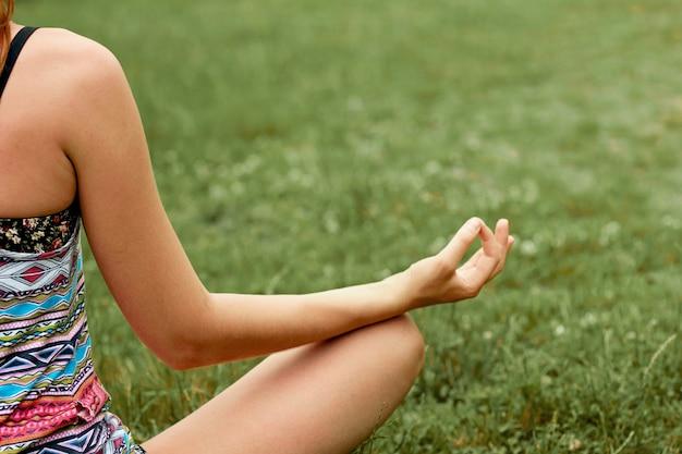 Jovem mulher fazendo ioga no parque de manhã. meditação. estilo de vida ativo. conceito de saudável e ioga. fitness e spo