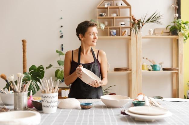 Jovem mulher fazendo louças de cerâmica e cerâmica na oficina