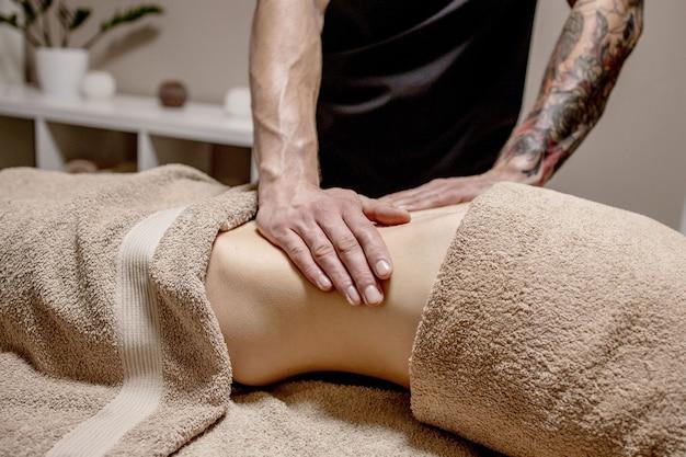 Jovem mulher fazendo massagem no abdômen. massagista faz massagem para estômago.