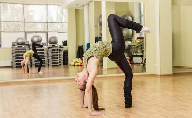Jovem mulher fazendo pé dividido na aula de fitness