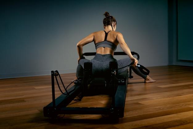 Jovem mulher fazendo pilates exercícios com uma cama de reformador. instrutor de fitness magro bonito. conceito de fitness