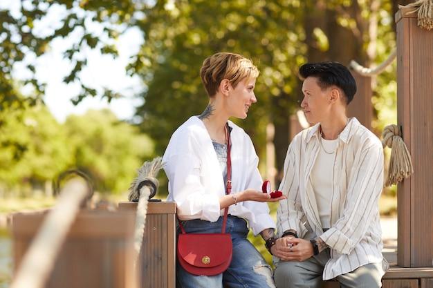Jovem mulher fazendo proposta para a namorada enquanto eles estão sentados no parque