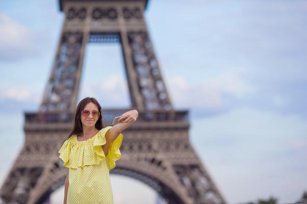 Jovem mulher fazendo selfie - auto-retrato por telefone na torre eiffel em paris