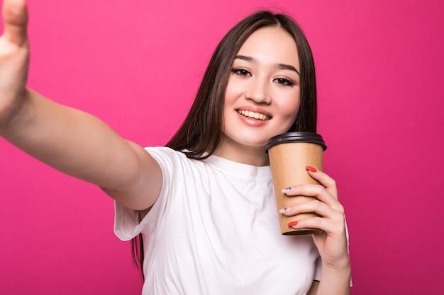 Jovem mulher fazendo selfie com sua xícara de café na parede rosa.