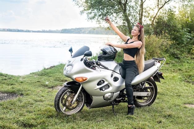 Jovem mulher fazendo selfie em uma moto ao ar livre