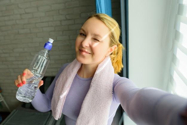 Jovem mulher fazendo selfies após treino. menina atrativa de sorriso da aptidão com toalha e garrafa de água após o treinamento.