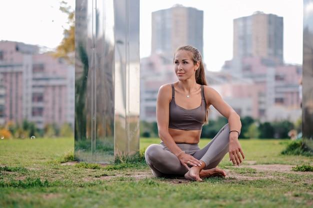 Jovem mulher fazendo sentado na pose de ioga com cidade no fundo.