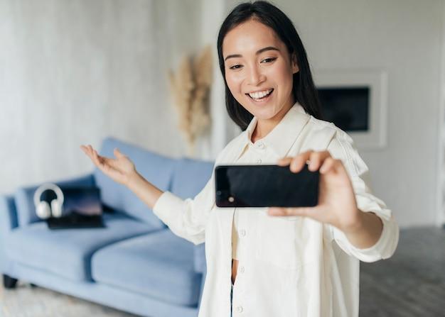 Jovem mulher fazendo streaming online com seu telefone