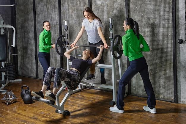 Jovem mulher fazendo supino com ajuda de assistentes. as mulheres brancas estão envolvidas no levantamento de peso na academia.